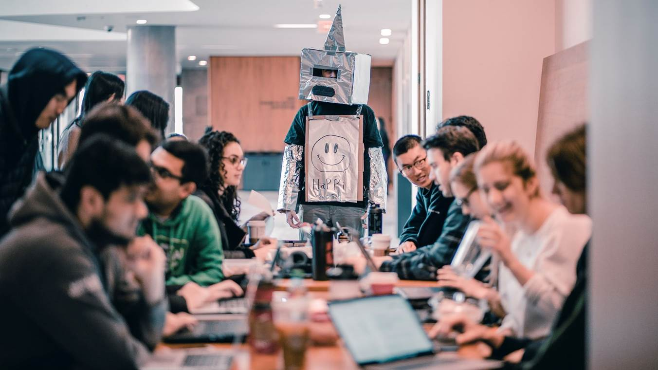 Students Studying With One Of Them Dressed In A Robot Suit