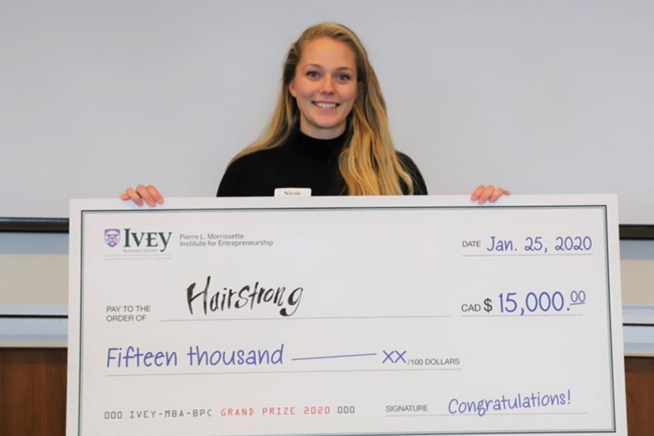 Hairstrong Founder Holding Winning Cheque For 2020 Business Plan Competition